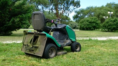 Green grass trimming with lawn mower. Tractor mowing grass in a public park. A dirty lawn tractor after mowing the lawn stands on the meadow. Professional lawn mower cuts the grass.