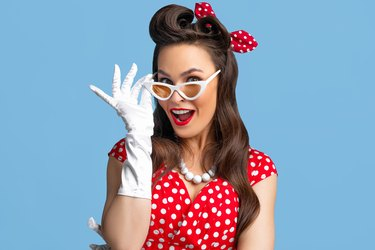 Portrait of excited pin up woman in polka dot dress, headband and gloves touching her sunglasses on blue background