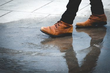 Low Section Of Man Walking On Wet Footpath