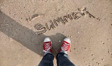In the photo taken from above, the inscription of the word summer on wet sand washed by the sea wave