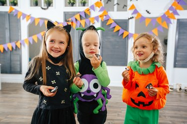 Children in Halloween costumes and with masks on are playing trick or treat and laughing.