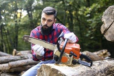 Lumberjack checking his chainsaw