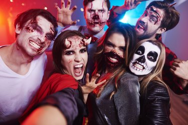Friends in creepy costumes having fun at Halloween party
