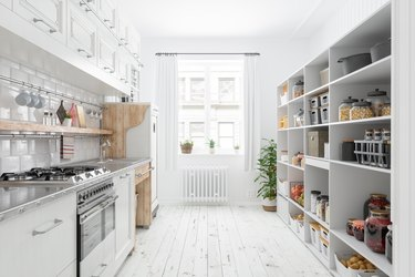Modern Kitchen Interior With White Cabinets And Organised Pantry Items, Nonperishable Food Staples, Preserved Foods, Healthy Eating, Fruits And Vegetables In Storage Compartment.