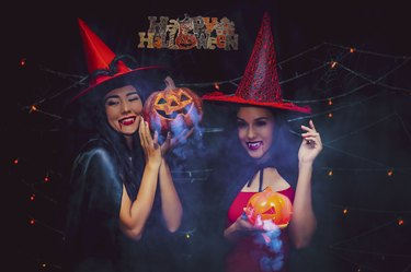 Vampire girls holding pumkin with darkness background