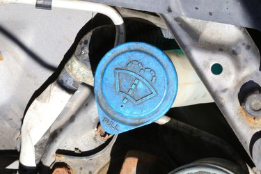 Windshield washer fluid access cap in a vehicle