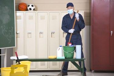 Senior Adult Janitor mops floor in school locker room.