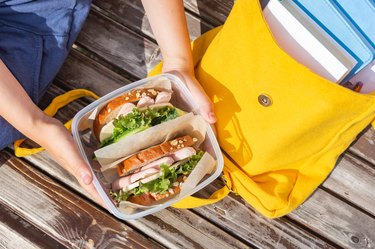 Lunch box in the hands of a child. Sandwiches  in a plastic container. Snack, school breakfast. Back to school. Lunch break.Yellow backpack with books
