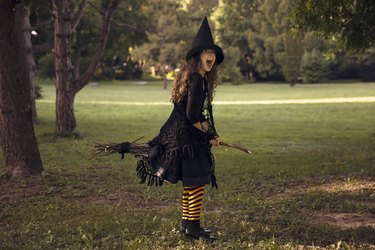 Little girl in witch costume and black long hat holding wooden broom, standing outdoor against autumn forest background.