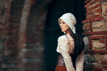 Medieval Woman in Historical Costume Wearing Corset Dress and Bonnet