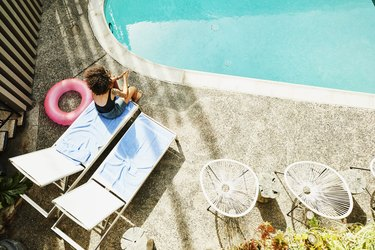 Overhead view of woman sitting on edge of lounge chair by pool