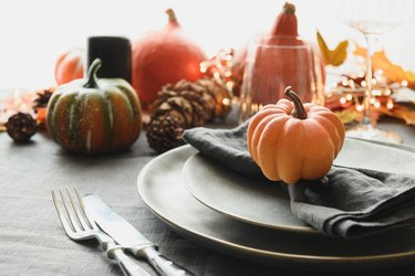 Halloween and Thanksgiving day dinner decorated fallen leaves, pumpkins, spices, grey plate.