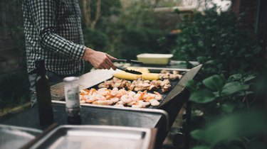 Grilling shrimp, meat and vegetables on barbecue