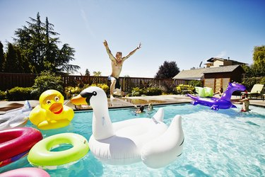 Man with jumping into pool during party