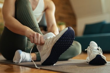 Close-up of athletic woman putting on sneakers.