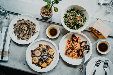 Flat lay of meal for two people with fresh green salad, appetizer, seafood linguine and beef ravioli freshly served on dining table in a restaurant