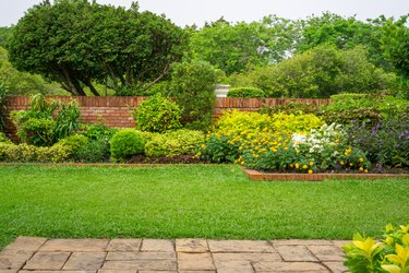 Backyard English cottage garden, colorful flowering plant and green grass lawn, brown pavement and orange brick wall, evergreen trees on background, in good care maintenance landscaping in park
