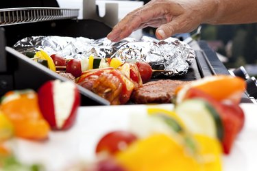 Vegetarian skewers and meat on barbecue grill