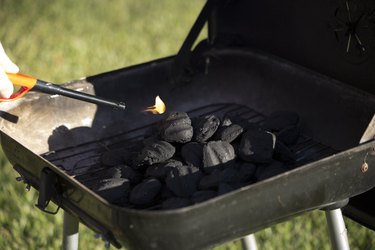 Cropped hand igniting barbecue grill