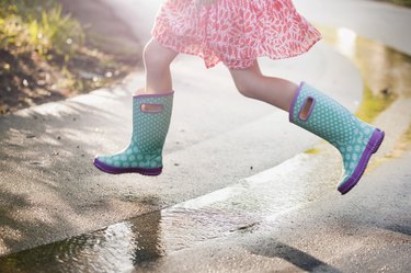 Waist-down view of girl jumping puddles in rain