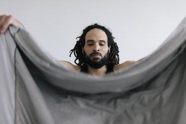 Man folding Bed sheets