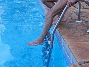 Man on ladder in swimming pool