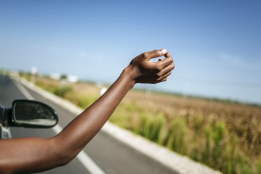 Hand of a woman leaning out of car window
