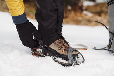 Man putting on crampons in the snow