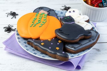 Halloween gingerbreads, pumpkin, tombstone, witch hat, black cat on a plate over wooden table
