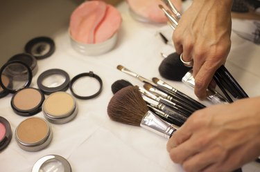 Make-up artist sorting through brushes on a table