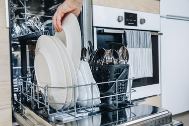 Woman loading the dishwasher. Open dishwasher with clean glasses and dishes close-up after washing.