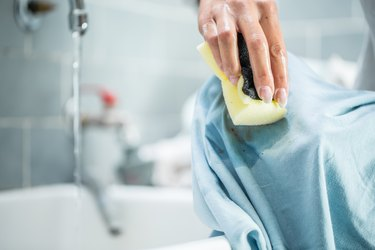Woman Cleaning Stained Clothing With Cleaning Sponge