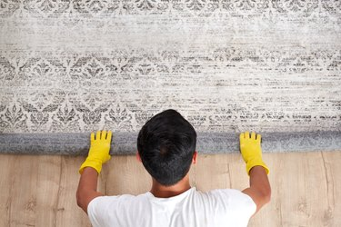 High angle view of man unrolling carpet. Cleaning service concept
