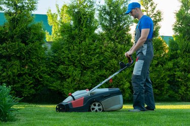 Young gardener in overalls uses a lawn mower on the plot