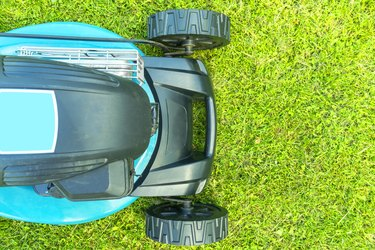Mowing lawns. Lawn mower on green grass. Mower grass equipment. Mowing gardener care work tool close up view. Sunny day.