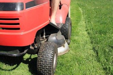 Red riding lawn mower (lawnmower, ride-on mower) in garden.
