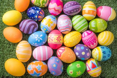Happy Easter with colorful eggs at paintbrush for do it yourself on the grass with close up from top view