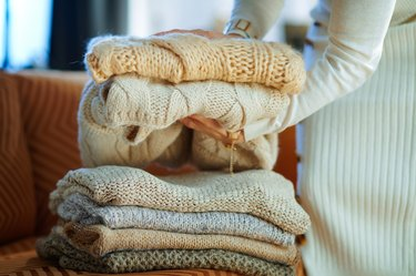 Closeup on woman near couch folding sweaters for storage