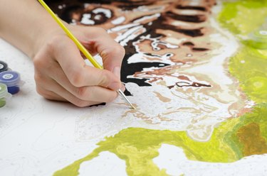 Woman's hand holding a brush for drawing close-up