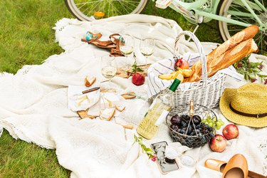 Summer - french style outdoor picnic in the garden. Wicker basket, food and wine.