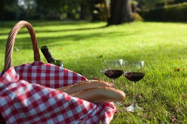Picnic Basket with baguettes and glasses of wine on grass
