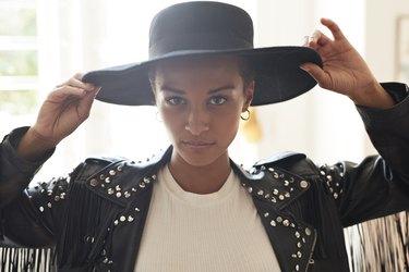 Portrait of confident young woman holding black hat