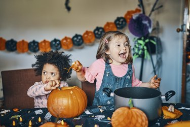 Two children at a table with a pumpkin taking out the middle and laughing.