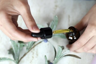 Hands holding pipette of essential oil