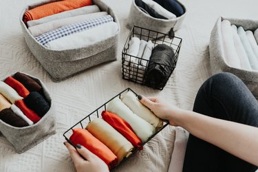 Folding clothes and organizing stuff in boxes and baskets. Concept of tidiness, minimalist lifestyle and japanese t-shirt folding system.