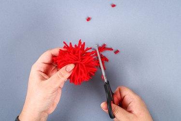 Red handmade diy monster pom pom from yarn, chenille stems in shape heart.