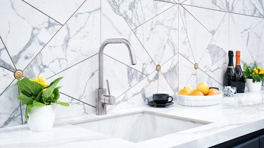 The interior of the modern kitchen is illuminated with a gray stone countertop with a luxury washbasin and mixer, fruit orange and flowers, a bottle with red wine, champagne and chocolate