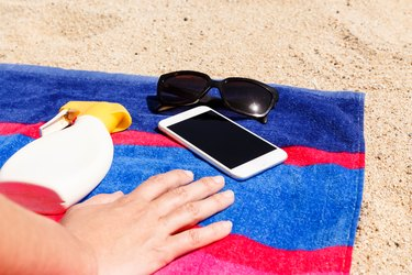Cropped Hand By Mobile Phone On Towel At Beach During Sunny Day