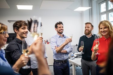 Happy business professionals with champagne flutes in office