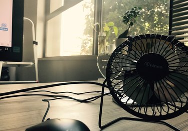 Electric Fan On Table By Window At Home